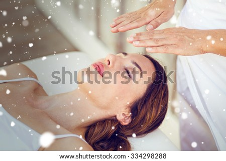Snow against calm woman receiving reiki treatment - stock photo