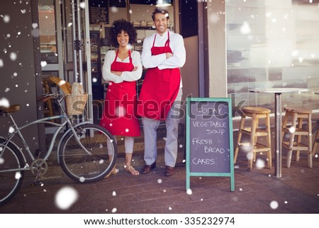 Snow against smiling colleagues in red apron with arms crossed - stock photo