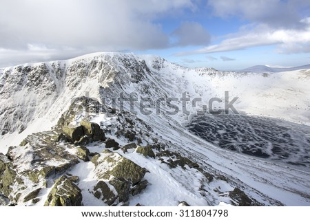 snow and ice covered mountains with frozen lake in helvellyn, cumbria - stock photo