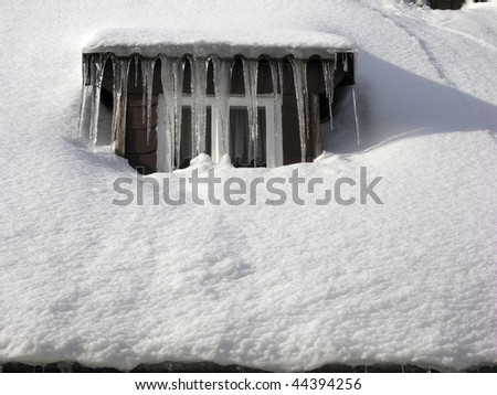 Snow and icicles all over window and roof. - stock photo