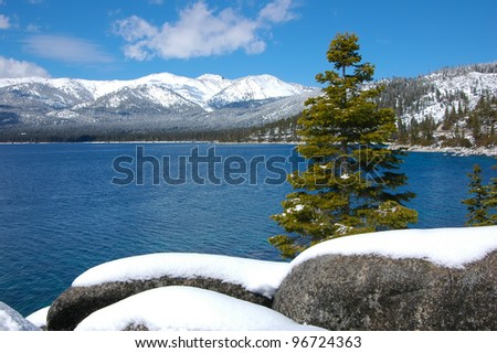 Snow at Lake Tahoe Photo of lake Tahoe after a heavy snow. The mountains at the other side are all covered by the snow. - stock photo