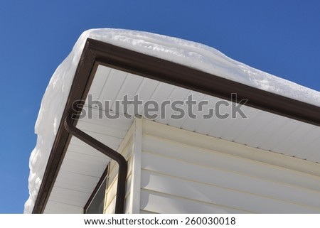 Snow at the edge of the roof - stock photo