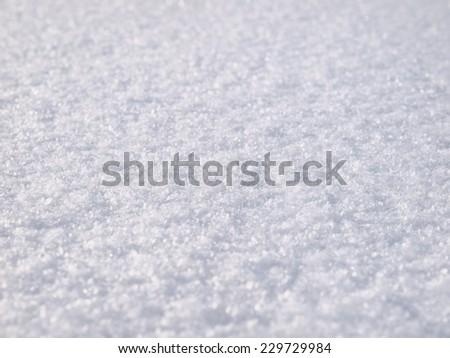 Snow background, white snowdrift surface texture closeup with selective focus, bokeh - stock photo