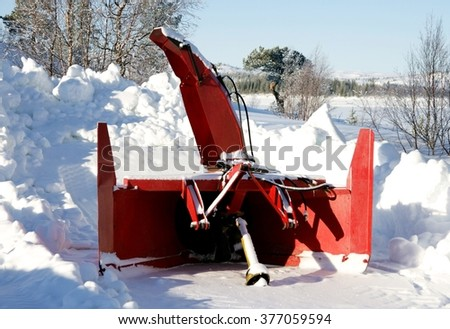 Snow blower parked in a Snowy landscape
