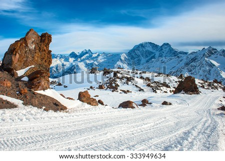 Snow blue mountains in clouds. Slope on winter ski resort - stock photo