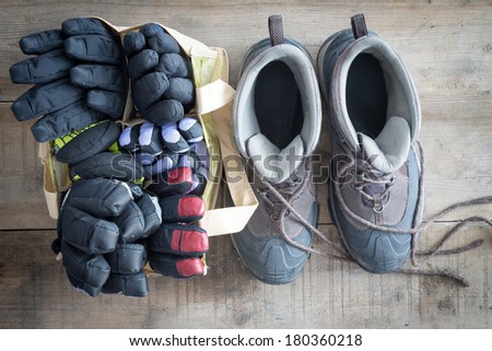 Snow boots with the laces lying free and a bag of winter gloves and mittens standing ready side by side on the floor of a rustic cabin, overhead view - stock photo