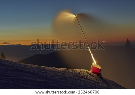 Snow cannon active at twilight on a ski slope in Poiana Brasov winter resort, Romania. Dark scenery. Night long exposure. - stock photo