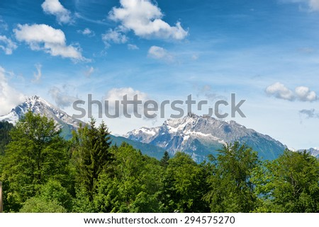 Snow-capped alpine peaks in the Berchtesgaden National Park, Bavaria, Germany in a scenic landscape under a cloudy blue sky - stock photo