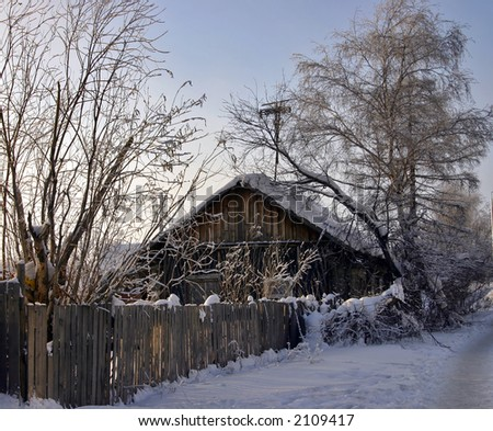 snow-capped log cabin in surroundings trees and fence on a background clear sky