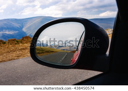 Snow-capped mountains in the reflection of the side mirror of the car. Autotravel. Elbrus - stock photo