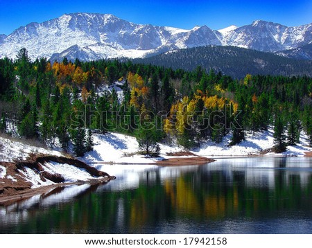 Snow capped Pikes Peak at Crystal Reservoir with Autumn leaves reflection