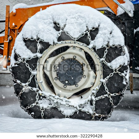 Snow chain on a cars tyre - stock photo