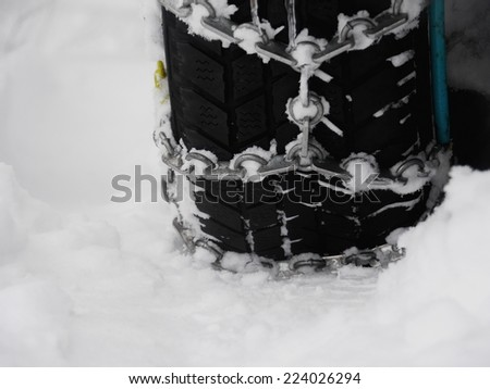 Snow chains outside at a wheel in winter - stock photo