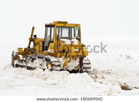 snow cleaning with caterpillar - stock photo