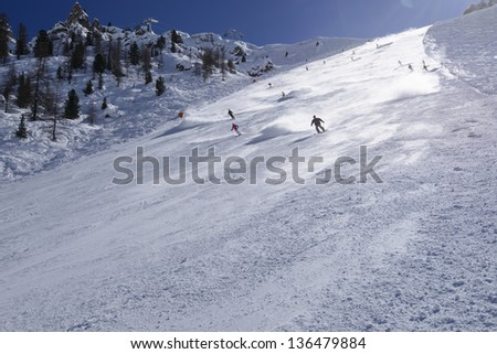 snow clouds on steep ski run #1, Arabba; skiers lift steamy clouds of snow descending steep slope in Dolomites, shot in back-light - stock photo