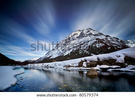 Snow covered alpine mountain with moving clouds in the sky - stock photo