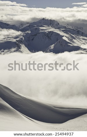 Snow covered alpine peaks at altitude surrounded by low cloud; snow in the foreground.