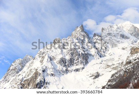 snow covered alps on a sunny winter day with blue sky and white clouds on the Italian side of the Mont Blanc tunnel