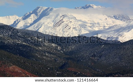 Snow covered Atlas Mountains and pine forest  between Marrakesh and Ouarzazate. - stock photo