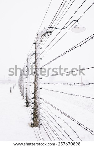 Snow covered Barbed Wire Fence in winter in the concentration camp of Auschwitz Birkenau, Poland - stock photo