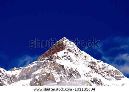 Snow covered beautiful mountain peaks against the blue sky - stock photo