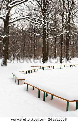 snow-covered benches in meadow of city park in winter - stock photo