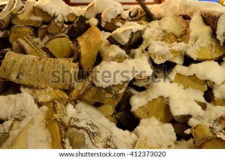 snow covered birch tree firewood logs - stock photo