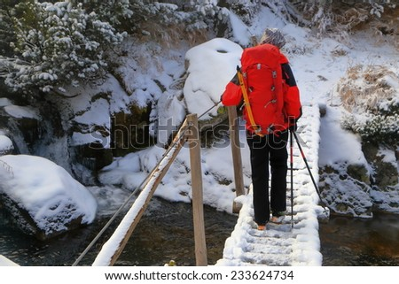 Snow covered bridge across the water with woman hiker carrying a backpack - stock photo