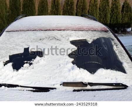 Snow covered car front window partly cleaned both sides, horizontal - stock photo