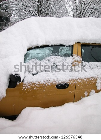 Snow covered car in a winter day - stock photo