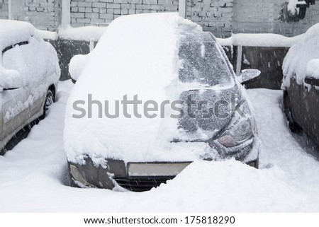 Snow-covered car in the parking lot. Urban scene. After a snowstorm. Clean automobile from the snow. - stock photo