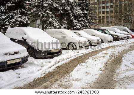 Snow covered cars in the street - stock photo
