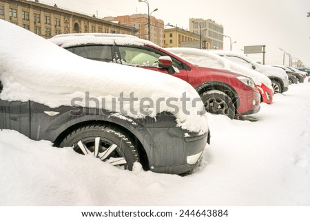 Snow covered cars in the street on the parking - stock photo