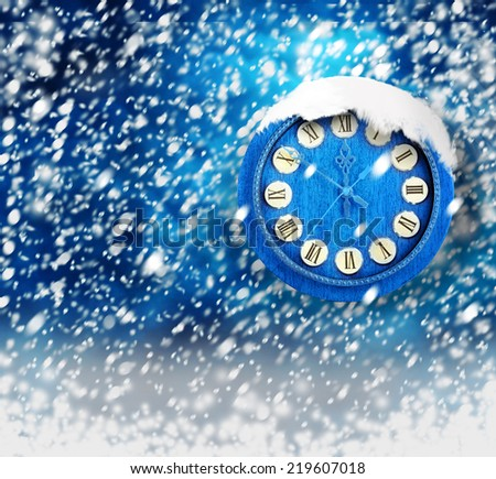 Snow-covered clock on abstract blue background - stock photo