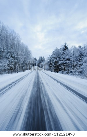 Snow covered country road from below in motion blur - stock photo