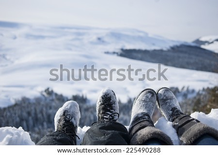 snow-covered feet of two hikers on a winter landscape. - stock photo