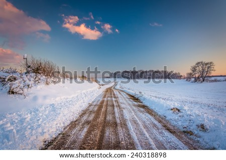 Snow covered field along a dirt road at sunset, in rural York County, Pennsylvania. - stock photo