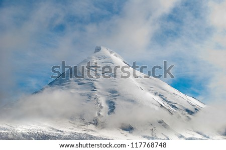Snow-covered high volcano in clouds located on Kamchatka