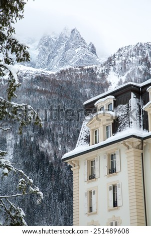 Snow covered house and the mountains, French Alps, France - stock photo