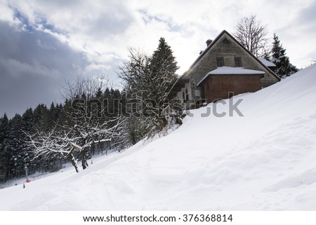 Snow covered house in a frosty mountains country in sunny winter day - stock photo