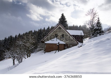 Snow covered house in a frosty mountains country in sunny winter day