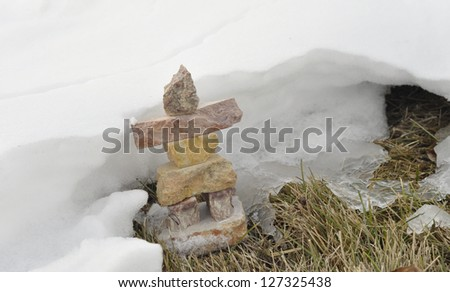 snow covered inukshuk in cold winter scene - stock photo