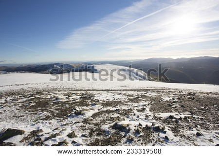 snow covered mountain plateau in bright sunlight at helvellyn, cumbria  - stock photo
