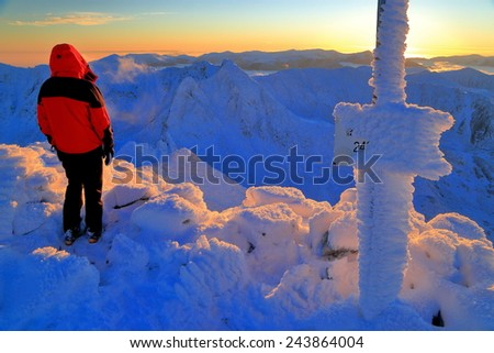 Snow covered ,mountain summit with hiker standing and watching the sunset - stock photo