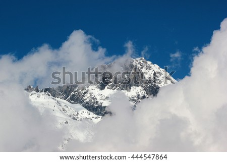 Snow covered mountains against white clouds and blue sky, Georgia, Caucasus - stock photo