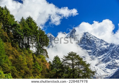 Snow covered mountains and rocky peaks in Himalaya - stock photo