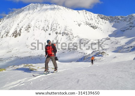 Snow covered mountains and ski mountaineers along sunny trail - stock photo