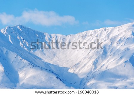 Snow covered mountains, blue sky, Alaska. - stock photo