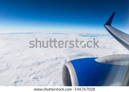 Snow-covered mountains from the plane window - stock photo