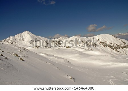 Snow covered mountains in a sunny day. Retezat mountains in the Carpathians. Romania - stock photo